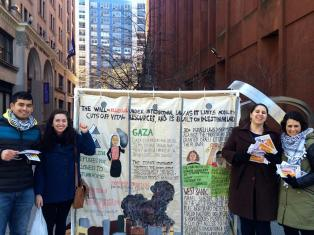 NYU-SJP members hand out flyers next to a mock Apartheid Wall, calling attention to the massive barrier Israel has built in the Palestinian West Bank to confiscate land and restrict movement. The Israeli Apartheid wall in Palestine is illegal under international law.